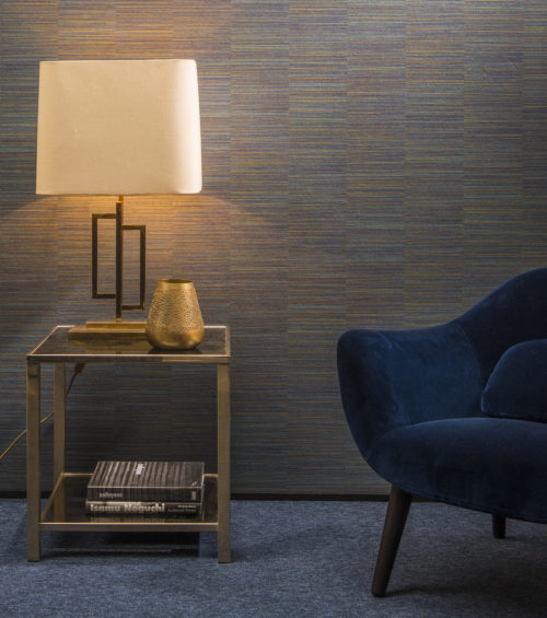 Dark blue Omexco Avenue wallcovering, night blue velvet chair, golden table with cream coloured lamp.