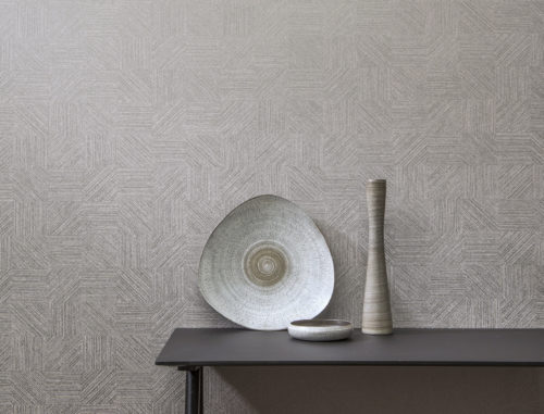 Ethnic interior detail with grey accessories: plate, bowl and vase. Omexco Avenue wallcoverings.