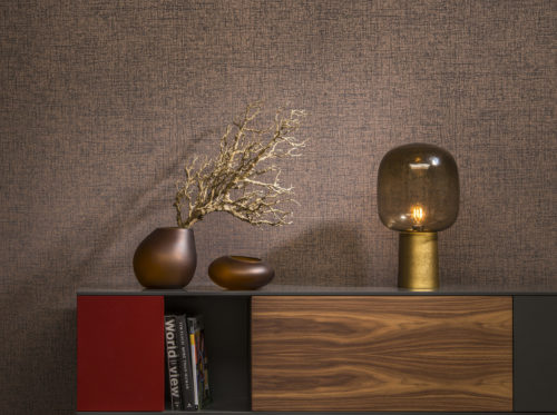 Copper and brown hues in this interior with brown glass lamp, copper vases. Console with book 'World View'.