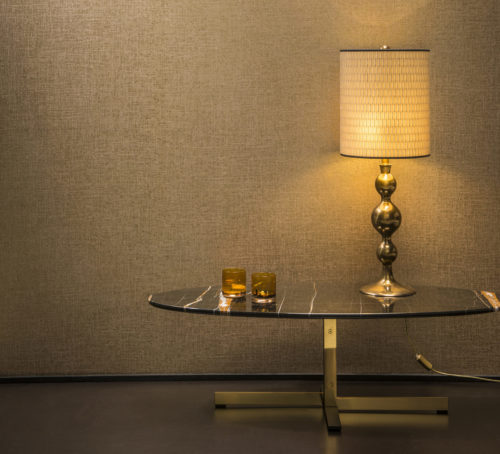 Warm interior picture of a marble table with golden legs. On the table a golden lamp. The foil in the Avenue wallcovering behind it shimmers gold.