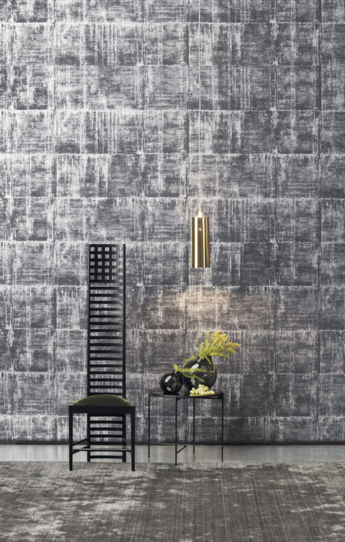 Wall with silver, grey and white Antarés wallcovering, black chair, little table and gold lamp