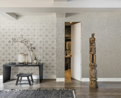 Asian inspired room with black table and wooden totem. Door to a little bathroom. Kork wallcovering on both walls.