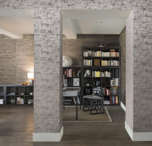 House library with large bookcase. Behind it grey waterlily wallcovering. On the wall leading to the room another Omexco, plain this time.