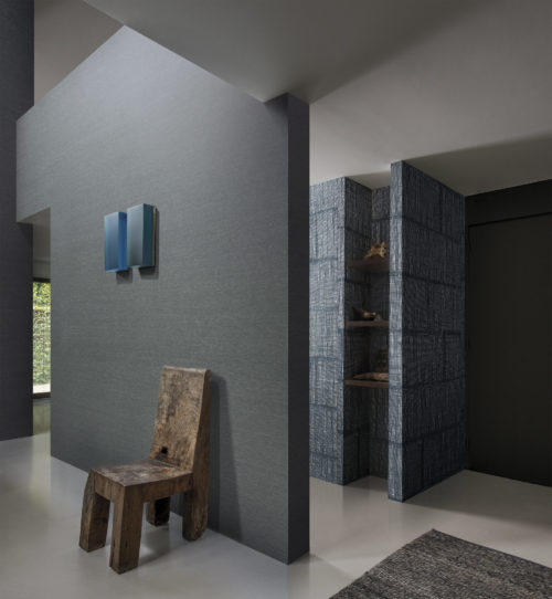 Hallway with a robust wooden chair. Above it a blue glass artwork. Blue raffia wallcovering forms a bookcase.