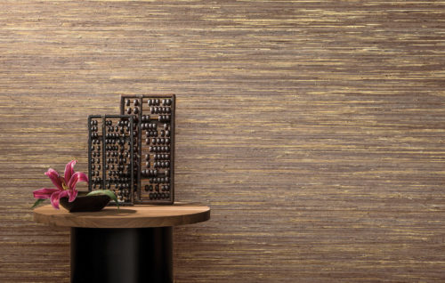 Splendid gold raffia wallcovering. Little round table with two abacusses in wood and an oval vase with fuchsia flower.