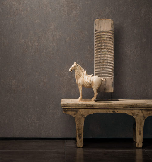 Warm decor with ethnic wooden table, artwork and horse. Dark brown Bijou plain wallcovering on the wall.