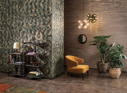 Tactile decor in earthly colours: green bakbak wallcovering, ocre chair, terracotta plant pots. Two pendant lamps bring out the gold shine in the raffia wallcovering on the far wall.