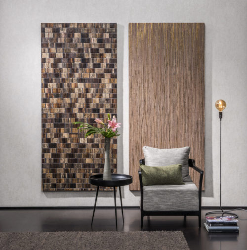 Plain wallcovering is the canvas for two outstanding wallcoverings: a brown bakbak and a golden raffia. A chair stands proudly in front of the wall art.