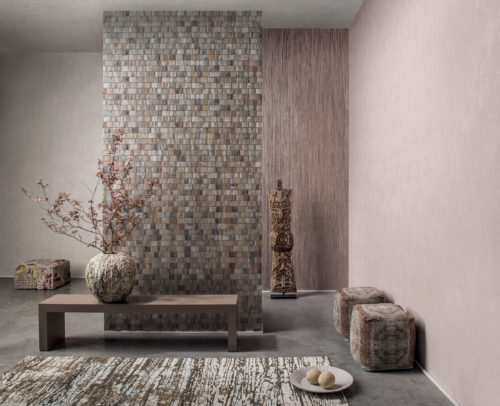 Ethnic interior in sand tones. Pixelated pouf, totem, carpet fabric poofs, structured vase with branch of blossoms.