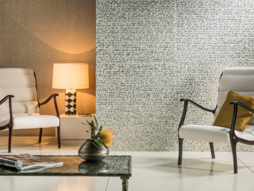 Classic room showing off two wallcoverings from the Capiz range by Omexco. One with real capiz shells, the other the dotted plain. A lamp with wide shade in the corner makes the metallic and the shells reflect. Two white leather chairs invite to sit and have a coffee.