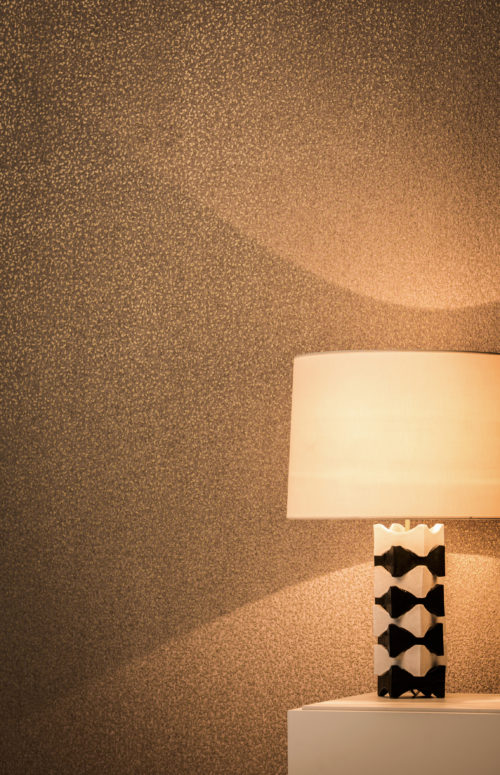 In the Omexco Capiz wallcovering range, we've also created a few non-woven wallcoverings. This dotted non-woven with brown and bronze relfects the ligth from the black-and-white standing lamp.