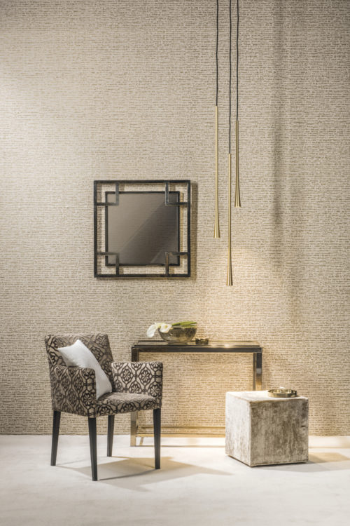 We want to show off the dotted stripe from our Capiz collection here. We've combined it with a chair with geometrical fabric and a mirror, also with geometrical frame. As golden drops, lamps come from the ceiling.