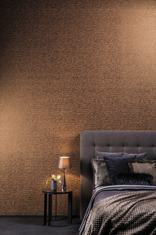 This wallcovering is a non-woven with a dotted stripe. The impressive colour of burnt orange combines well with the dark blue and grey velvet bed in this picture. A little lamp on the night stand makes the bronze foil reflect.