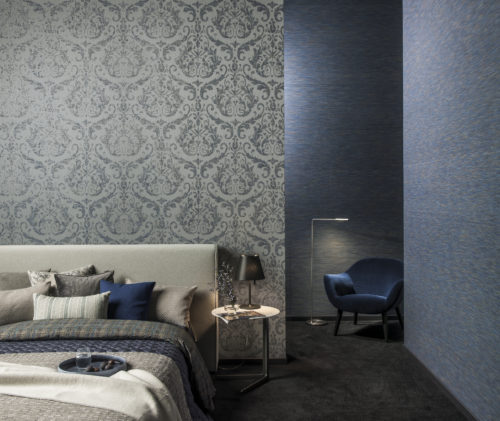 Tactile blue and grey bedroom. Soft pillows in different colours, plaids in different structures. In the corner a blue velvet chair with reading light. Warm carpet on the floor.
