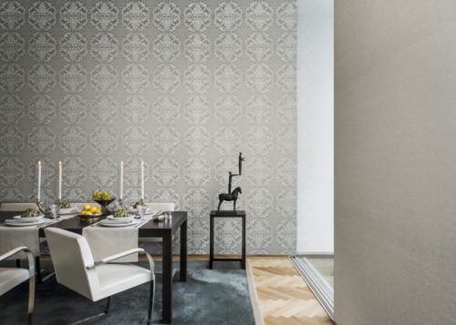 Dining room with a set table, ready for a lovely dinner. Impressive damask wallcovering from the Elegance range. Pedestal with a statue of a man standing on the hands of a man, standing on a horse.