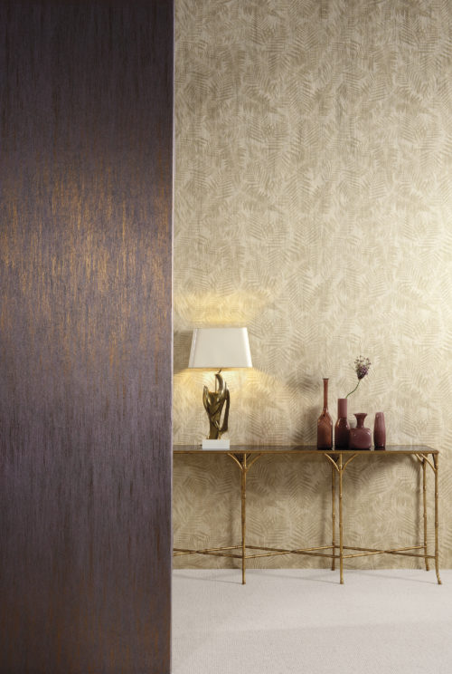 A beautiful play of light in this picture. In the front we see ELA113 Elixir wallcovering in purple with bronze foil. In the background a metallic fern motif. The slim brass legs of the console are in harmony with the wallcovering.