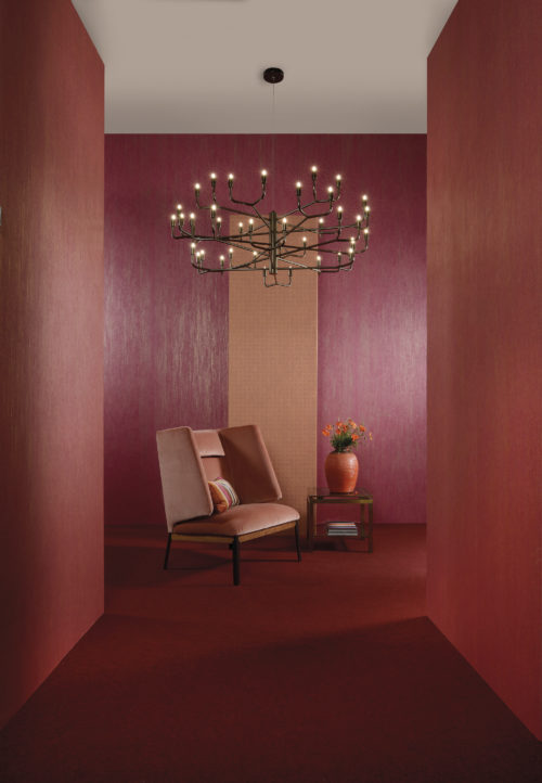 Cherry red and blushing orange wallcoverings from the Omexco Elixir range. Impressive velvet chair. Black chandelier with candle-like lights.
