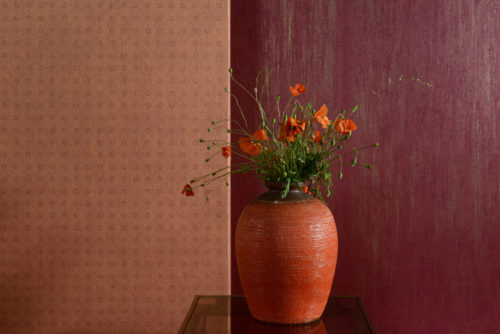 Cherry red and blushing orange wallcoverings from the Omexco Elixir range. Impressive bright orange vase with poppy flowers.