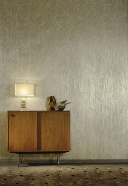 Detail of the a metallic fern motif from the Omexco Elixir range. We also see a wooden retro console and geometrical dark glass vase.