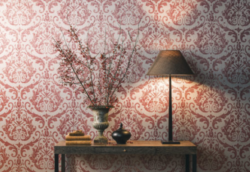 Nice setting bringing out the nice red damask in our Elegance wallcovering. Console with lamp, books, ceramic artwork and vase with berries.