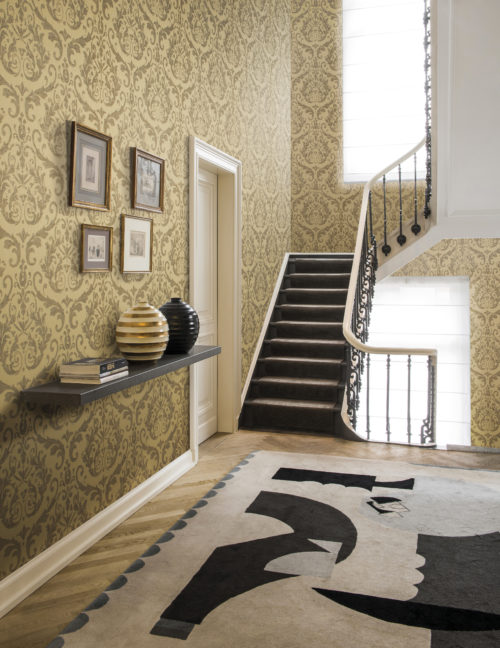 Impressive staircase with yellow and white gold damask wallcovering from the Omexco Elegance range. The contemporary abstract carpet on the wooden floor is in nice contrast with the classic design of the wallcovering
