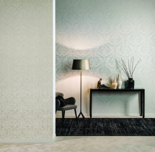 We look at a black carpet and black console. They stand out from the walls, dressed in white and beige damask wallcoverings by Omexco.