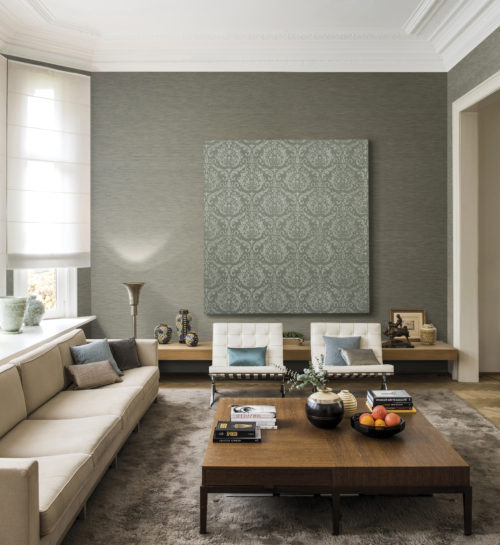 Living room with a high ceiling and big windows. 4 seater sofa and lounge chairs in cream. On the wall one plain wallcovering from the Elegance range and one damask installed on a frame. Standing out like a piece of art.