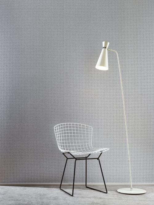 For this mica wallcovering in the Graphite range we've embossed grey mica with a silver foil in the form of little blocks. It goes well with other geometrical interior details like this white standing lamp and white wire chair.