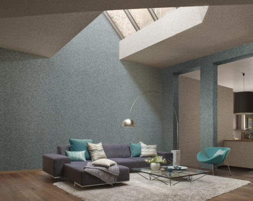 Vast living room with a lot of natural light from a glass piramid in the ceiling. Electric blue mica wallcovering on the wall. Large blue corner sofa with pillows in aqua tones.