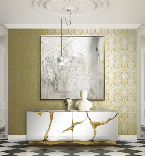 Yellow wall with silver damask, impressive shiny console with gold cracks, buste, pending lamp, silver painting. White and black checked floor.