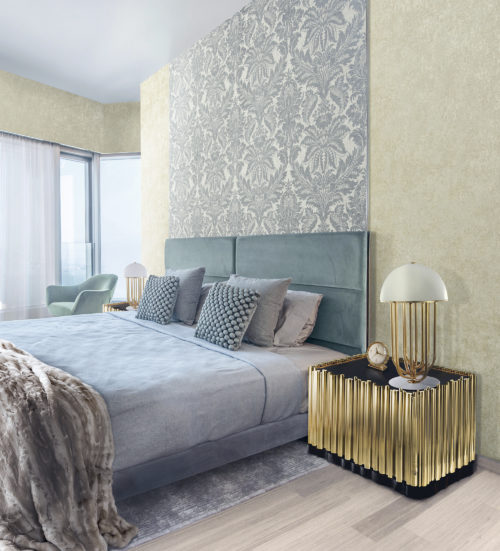 Light blue bedroom with textured pictures and a furry plaid. Golden nightstand with golden lamp. On the wall a light blue damask wallcovering by Omexco.