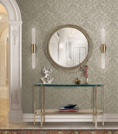 Wall in a hallway with mirror and two lamps on each side of the mirror. The mirror is decorated with cables. Console in glass and gold metal. Buste. Damast wallcovering on the wall.