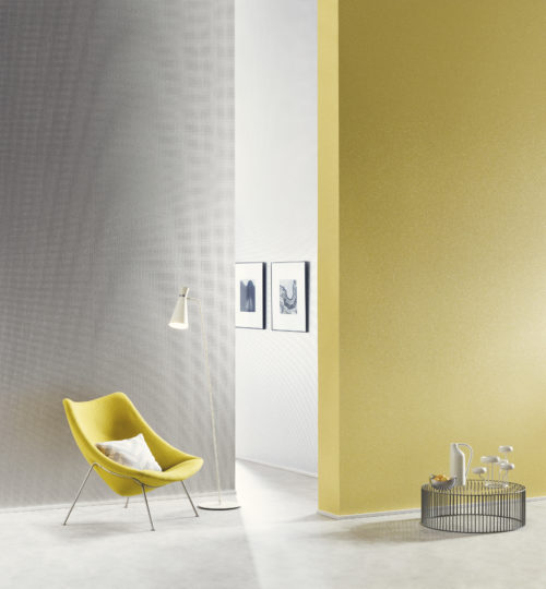 Lemon coloured wall with mica stones. Yellow lounge chair. On the far wall satin silver mica wallcovering with embossed square.