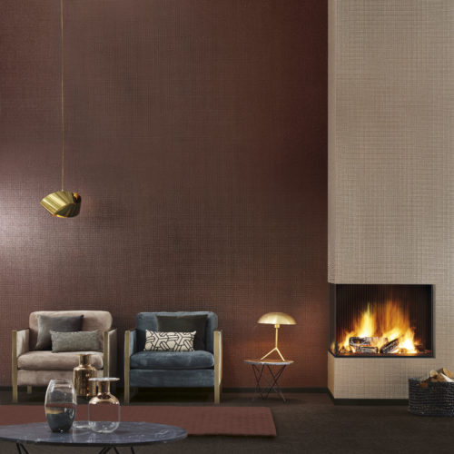 Warm interior picture of a living room with fire place. Two velvet lounge chairs. Impressive folded gold lamp. Two types of mica wallcoverings: one rust, one rosé gold.