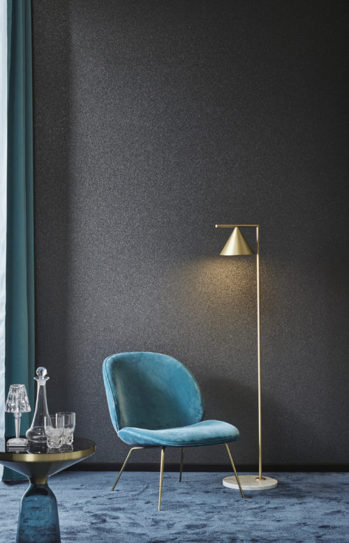 Dark grey mica stone wallcovering from the Omexco Graphite range. Turquoise chair and curtain. Little round table with glasses.