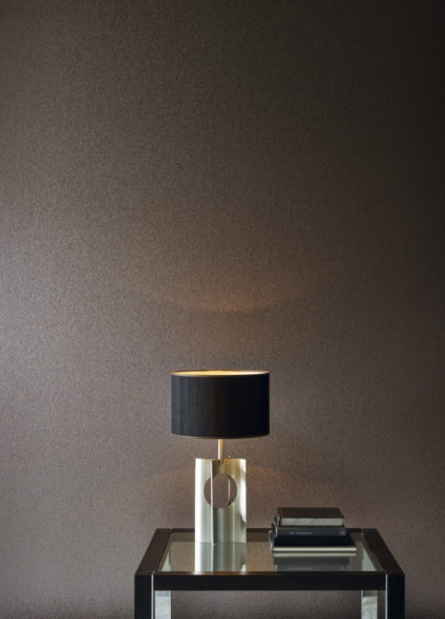 Impressive wall with small mica shells wallcovering from the Omexco Graphite range. Glass table with black details, black matt lamp shade and a few books.
