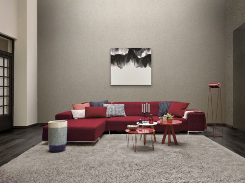 Interesting living room. Tall wall with silver mica wallcovering. Impressive black and white artwork. Red furniture adding to the wow factor.
