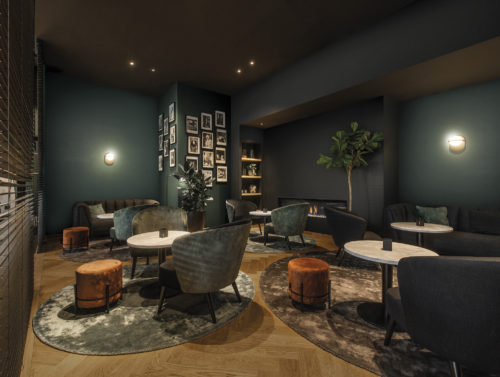 On the walls of this cosy, luxury hotel lounge: the Linen design in duck green and dark grey from Omexco's High Performance Textures collection.