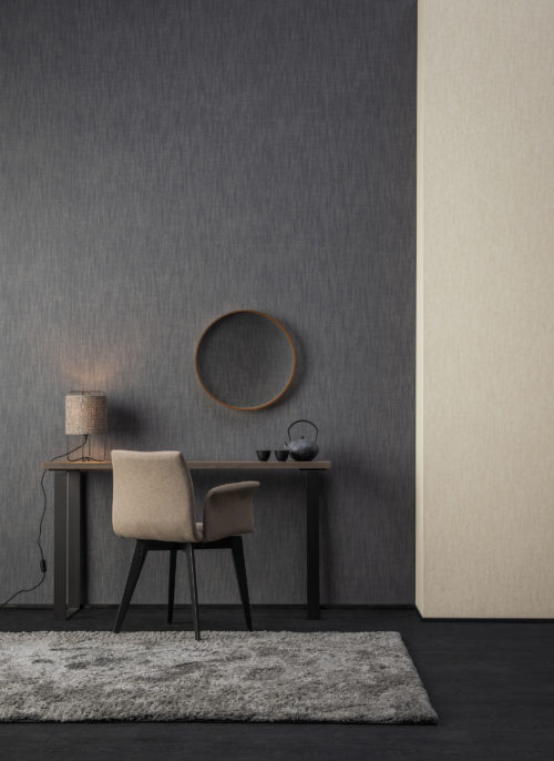 Hotel room where Omexco's High Performance Textures wallcoverings are installed. We see a desk with chair, round mirror, fluffy carpet and contrasting walls in dark grey and beige. Denim design, luxurious yet sustainable. Inspired by the technique used for jeans manufacturing with diagonal ribbing as a result.