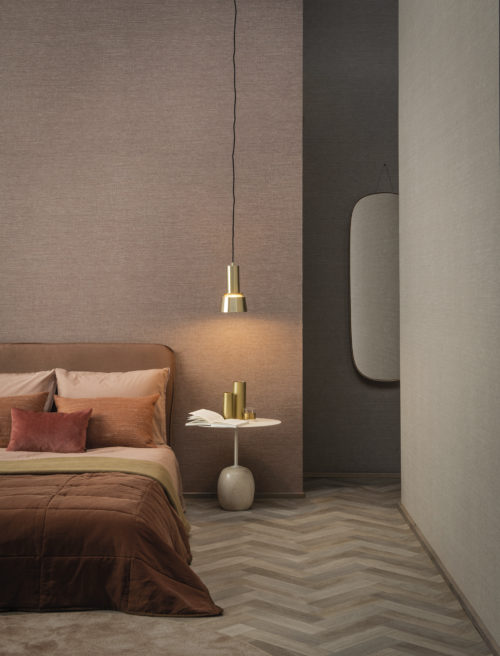 On the walls of this hotel room: the Abaca design in blush and beige hues from Omexco's High Performance Textures collection. It's a semi plain non-woven wallcovering with an intriguing texture, shown horizontally. The wallcovering is paired with a cosy bed, pendulum lamp, orange and beige pillows, mirror and a side table.