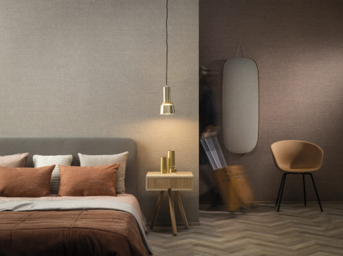 On the walls of this hotel room: the Abaca design in beige and blush hues from Omexco's High Performance Textures collection. It's a semi plain non-woven wallcovering with an intriguing texture, shown horizontally. The wallcovering is paired with a cosy bed, pendulum lamp, orange and beige pillows, orange chair and a wooden side table. Woven extra fine abaca. The abaca fibre we use as a grasscloth in Seraya and other collections is the inspiration.  It is the stem and supporting structure of the long leaves of the Abaca tree, a species of banana tree native to the Philippines.