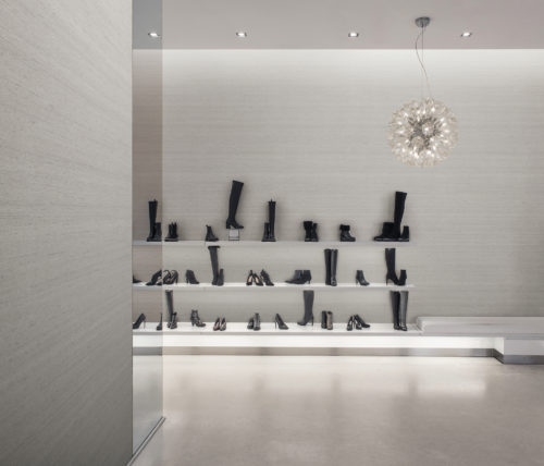 A contemporary, luxury shoe store with black boots and heels displayed against the wall. The perfect backdrop for the beige texture of the Tussah design of Omexco's High Performance Textures wallcoverings. Function meets beauty, durability meets luxury, sustainability meets high performance.