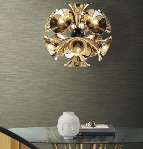 Round glass table with slim wooden legs. Porcelain vase with heads. Outstanding golden lamp. Inifnity wallcoverings.