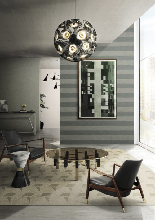 Living room with two leather chairs round a dark glass centre table. Outstanding chrome pendant lamp by Delightfull. Abstract painting. Infinity wallcoverings in grey shades.