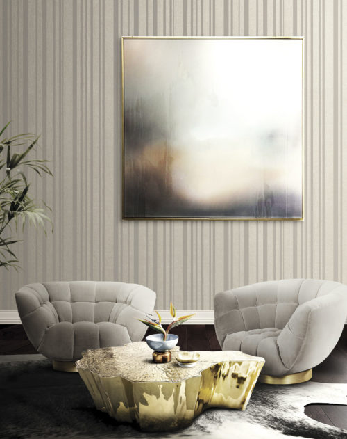 Tactile room with velvet chairs that make you think of hands to sit on. Vague pastel work of art, beige striped Infinity wallcovering.