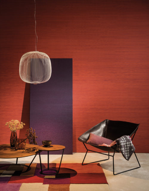 Interior in vibrant colours: purple and orange paper strips wallcovering. The room is brought to life by combining the wallcovering with the same colours in the carpet en pillows.