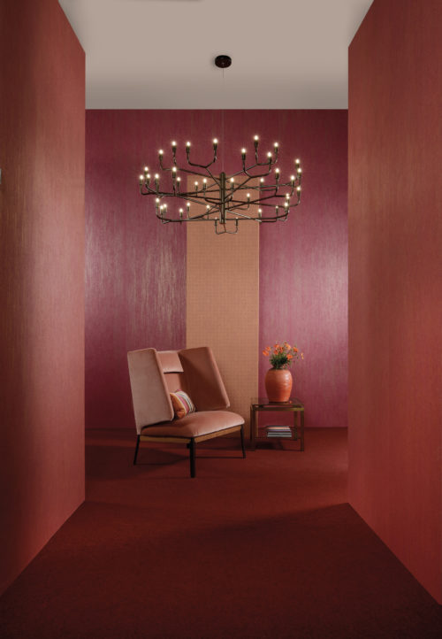 Cherry red and blushing orange wallcoverings. Impressive velvet chair. Black chandelier with candle-like lights.
