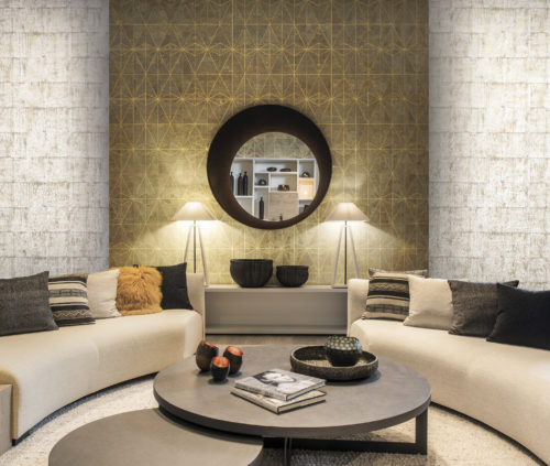 Impressive living room with two bended sofas hugging the round table and cosy pillows. On the walls: two exclusive wallcoverings from the Antarès and Khatam collection, a fusion of nature and precious metal, brings shimmering elegance and soft glamour to your walls.