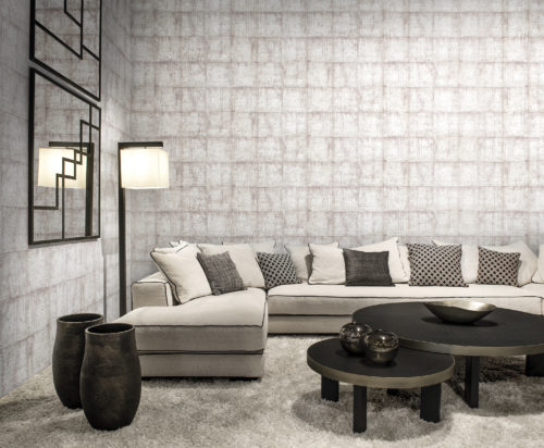 In this interior we show off the chequers design from our Khatam wallcovering collection: this classic design with a modern twist evokes the patina walls of Venetian palaces. Here it is combined with a sofa in the same white colour. Accessories are dark: black mirror, black standing lamp, dark brown vases, dark brown round coffee tables.