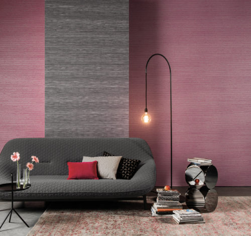 Two Koyori wallcoverings are combined here: a monochrome plain in black and a bicolour stripe pattern. A grey structured sofa, a pending standing lamp, piles of books and a chrome table make out this consoling interior.